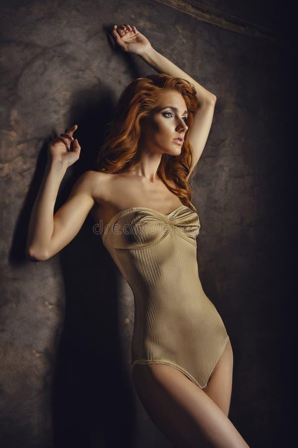 Femme d'une chevelure rouge dans la combinaison beige image libre de droits