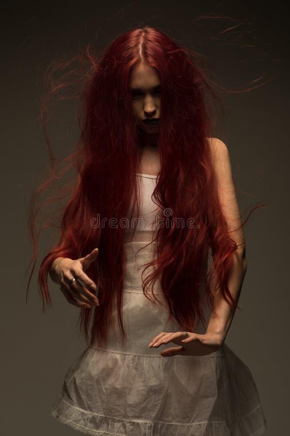 Femme d'une chevelure rouge de zombi dans la robe blanche de coton images stock