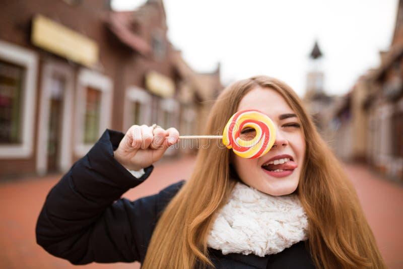 Femme d'une chevelure rouge drôle tenant la sucrerie colorée de Noël au s image libre de droits