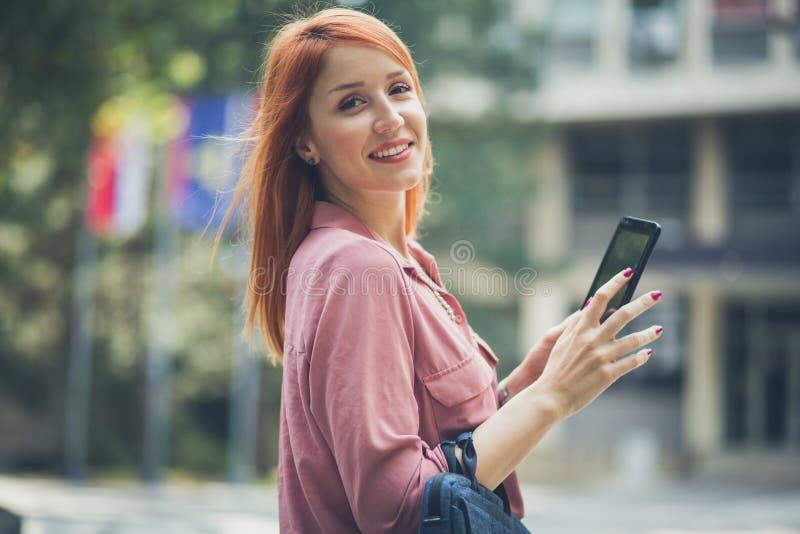 Femme d'une chevelure rouge regardant l'appareil-photo photo libre de droits