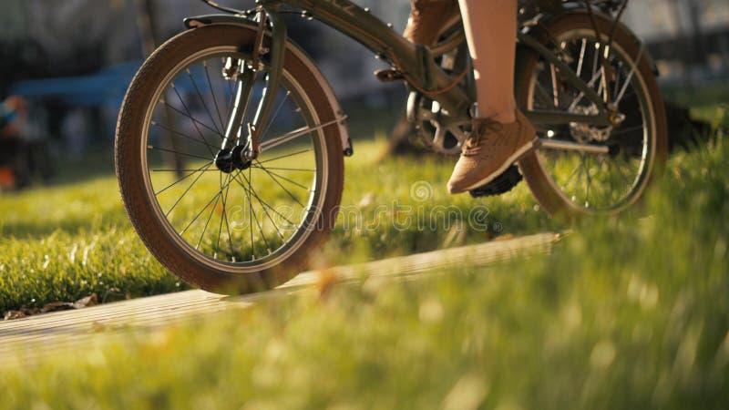 Femme d'une chevelure rouge s'asseyant sur la bicyclette se trouvant sur l'herbe en parc de ville Parc de vélo de femme photographie stock libre de droits