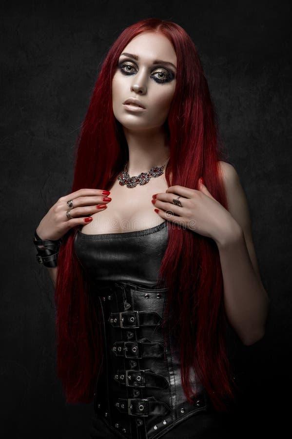Femme d'une chevelure rouge sexy dans des vêtements en cuir noirs image libre de droits