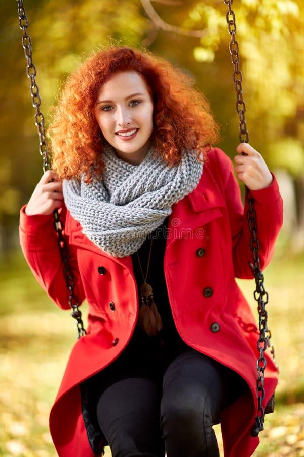 Femme d'une chevelure rouge sur une oscillation photographie stock
