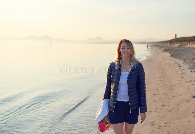 Femme d'une cinquantaine d'années attirante marchant sur une plage photographie stock libre de droits