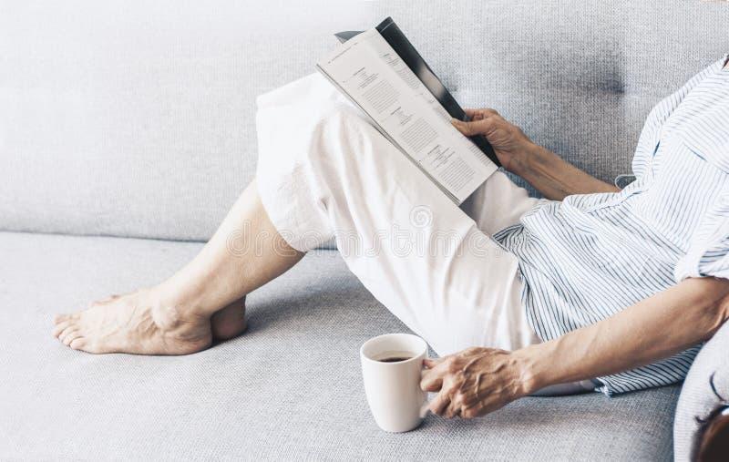 Femme d'une cinquantaine d'ann?es de brune sur la magazine grise de lecture de sofa avec la tasse de caf? photographie stock