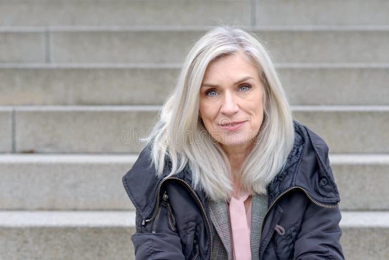 Femme d'une cinquantaine d'années occasionnelle s'asseyant sur des étapes extérieures image stock