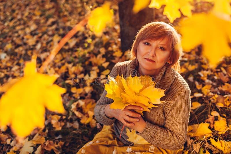Femme d'une cinquantaine d'années tenant le bouquet des feuilles d'érable Madame appréciant la nature et la détente d'automne photos libres de droits