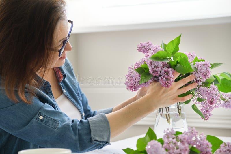 Femme d'une cinquantaine d'ann?es faisant le bouquet des branches lilas, groupe de arrangement femelle en gros plan de fleurs dan image stock