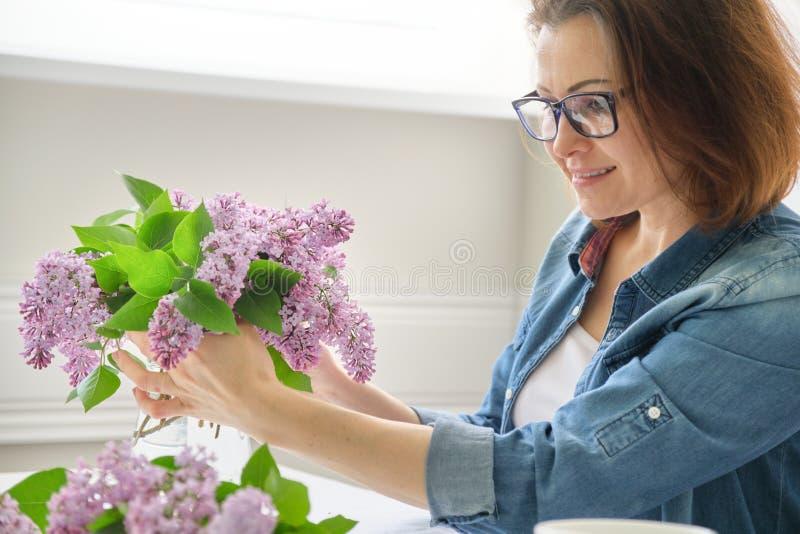 Femme d'une cinquantaine d'ann?es faisant le bouquet des branches lilas, groupe de arrangement femelle en gros plan de fleurs dan photos stock