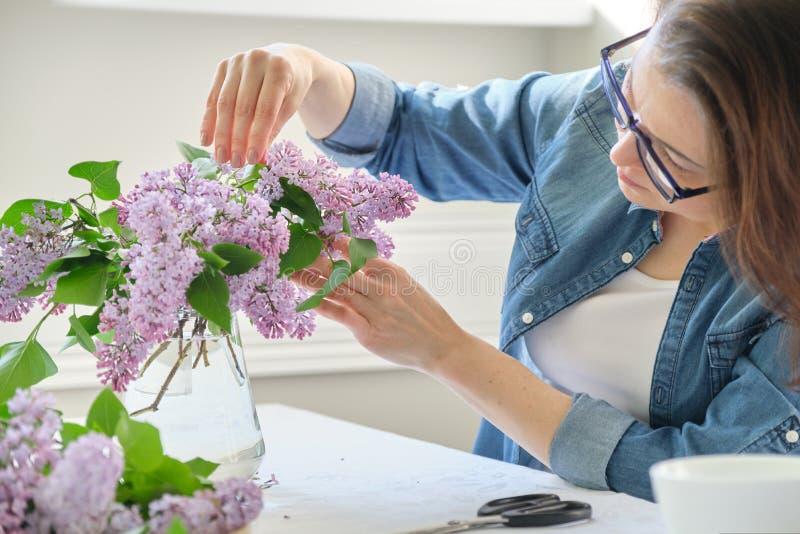 Femme d'une cinquantaine d'ann?es faisant le bouquet des branches lilas, groupe de arrangement femelle en gros plan de fleurs dan photos libres de droits