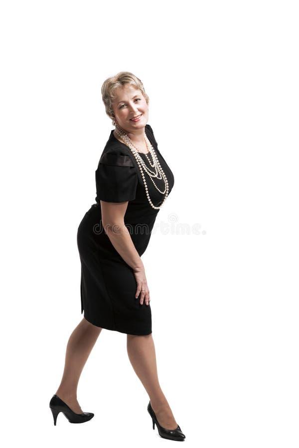 Femme d'une cinquantaine d'années attirante dans la robe noire photo libre de droits