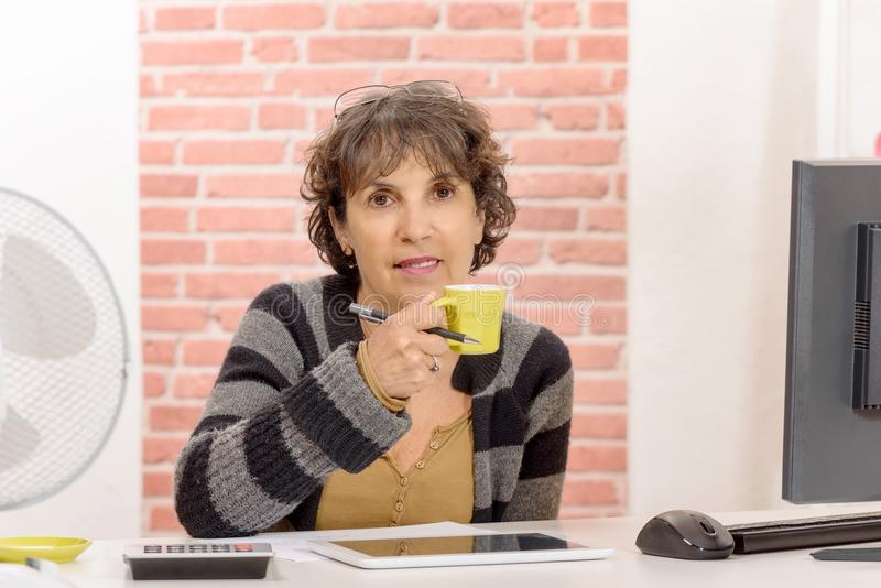 Femme d'une cinquantaine d'années avec du charme buvant d'un café image stock
