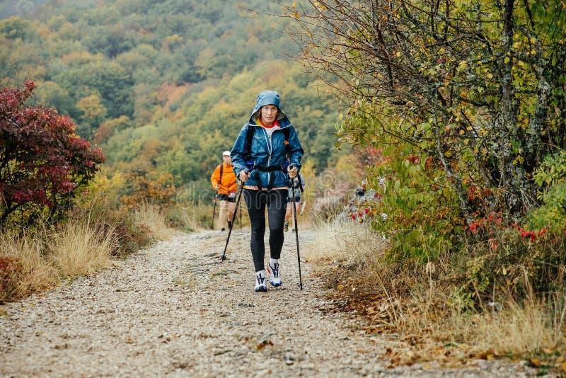 Femme d'une cinquantaine d'années avec les poteaux de marche voyageant par temps pluvieux sur la traînée de montagne photo libre de droits