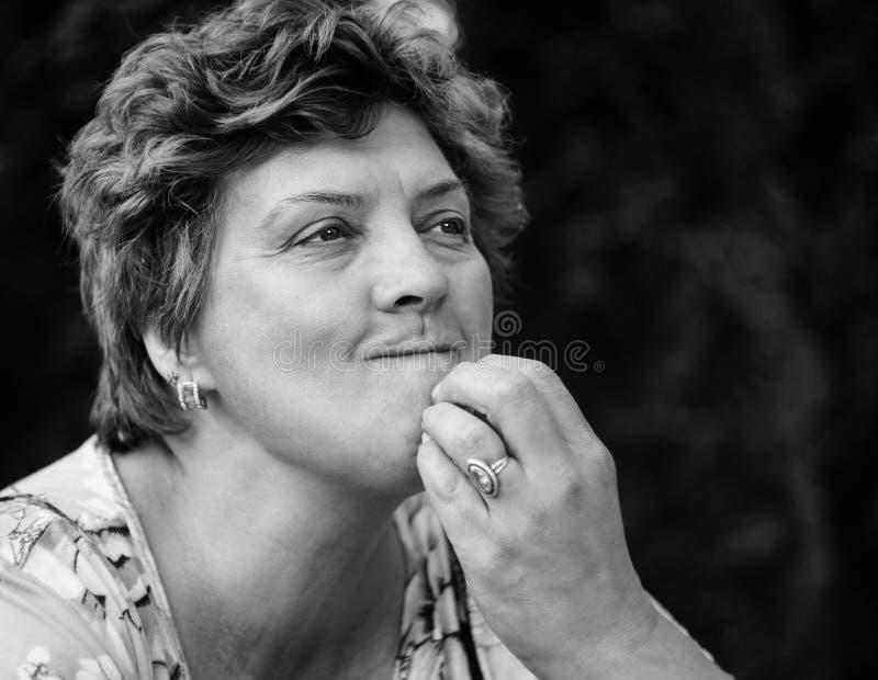 Femme d'une cinquantaine d'années posant sur un fond noir image libre de droits