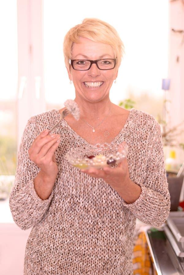 Femme d'une cinquantaine d'années vivace mangeant de la salade de fruits images libres de droits