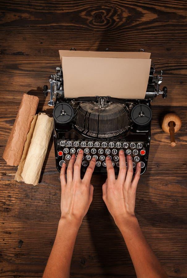 Femme dactylographiant sur une vieille machine à écrire photographie stock libre de droits