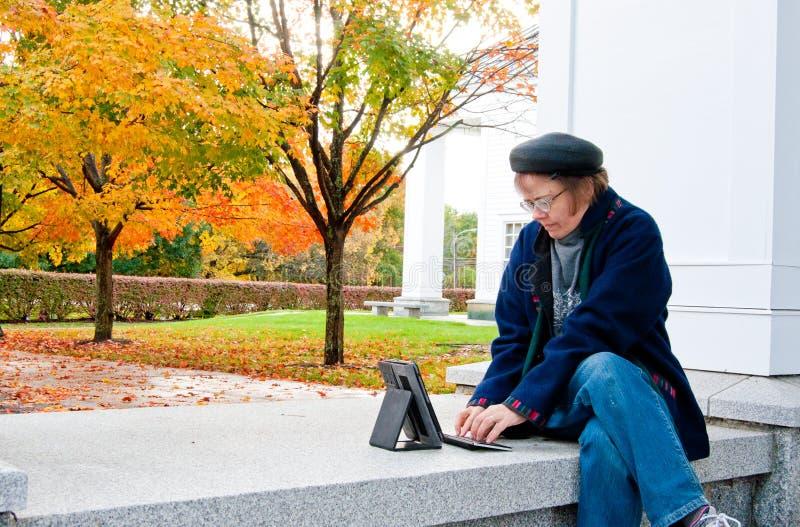 Femme dactylographiant une tâche sur le campus photos stock