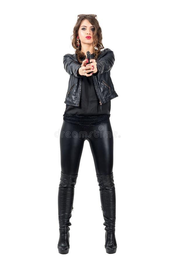 Femme dangereuse sexy dans les bottes en cuir et la veste noires dirigeant le pistolet à vous images libres de droits