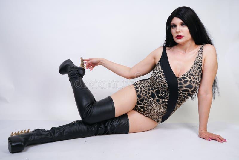 Femme dangereuse sexy de brune dans le maillot de bain de l?opard et bottes de cuisse en cuir hautes avec le talon squelettique s photographie stock