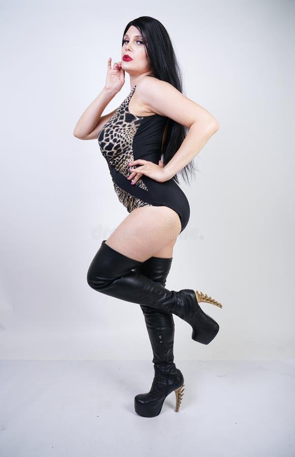 Femme dangereuse sexy de brune dans le maillot de bain de l?opard et bottes de cuisse en cuir hautes avec le talon squelettique s image stock