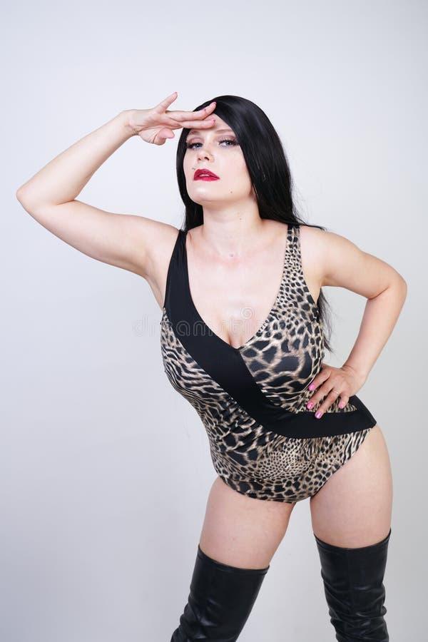Femme dangereuse sexy de brune dans le maillot de bain de l?opard et bottes de cuisse en cuir hautes avec le talon squelettique s images stock