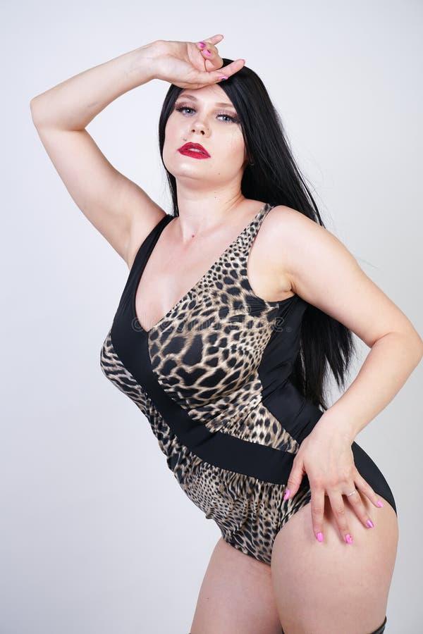 Femme dangereuse sexy de brune dans le maillot de bain de l?opard et bottes de cuisse en cuir hautes avec le talon squelettique s photographie stock libre de droits