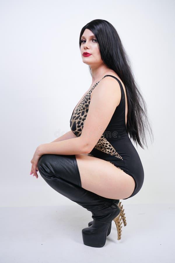 Femme dangereuse sexy de brune dans le maillot de bain de l?opard et bottes de cuisse en cuir hautes avec le talon squelettique s photos libres de droits