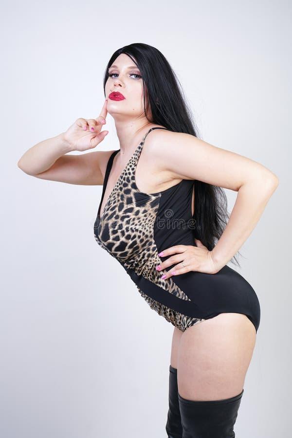 Femme dangereuse sexy de brune dans le maillot de bain de l?opard et bottes de cuisse en cuir hautes avec le talon squelettique s image libre de droits