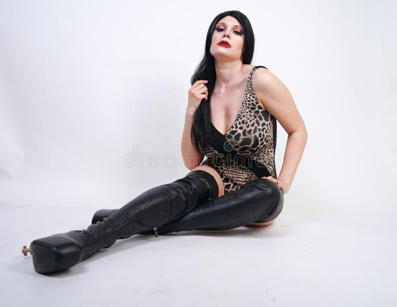 Femme dangereuse sexy de brune dans le maillot de bain de l?opard et bottes de cuisse en cuir hautes avec le talon squelettique s images libres de droits