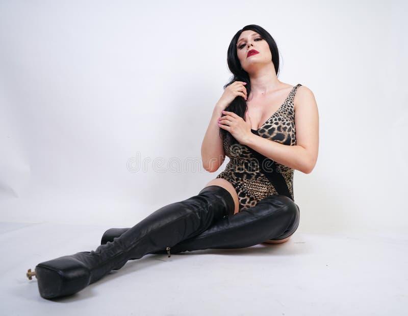 Femme dangereuse sexy de brune dans le maillot de bain de l?opard et bottes de cuisse en cuir hautes avec le talon squelettique s photos stock