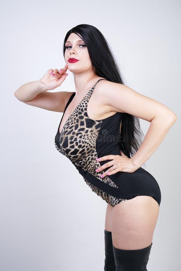 Femme dangereuse sexy de brune dans le maillot de bain de l?opard et bottes de cuisse en cuir hautes avec le talon squelettique s photo libre de droits