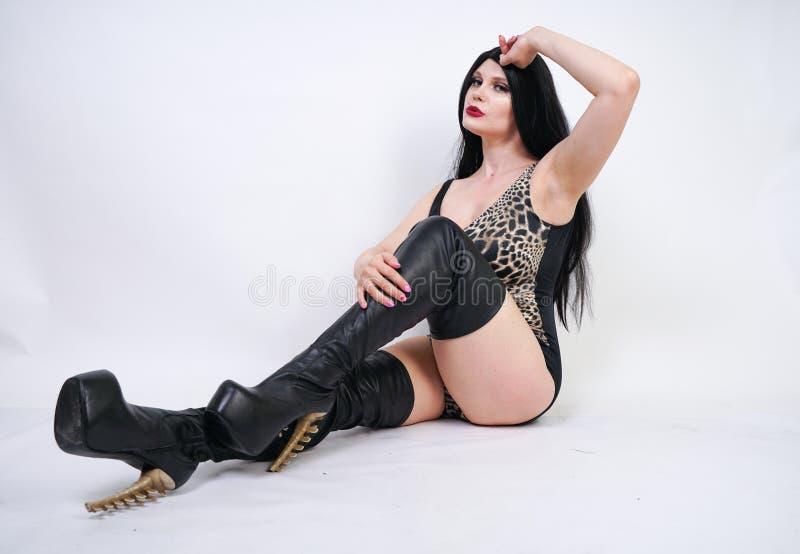 Femme dangereuse sexy de brune dans le maillot de bain de l?opard et bottes de cuisse en cuir hautes avec le talon squelettique s photo stock
