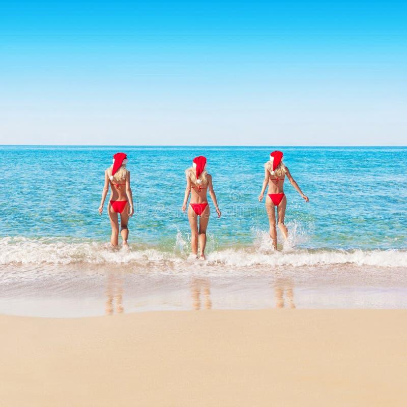 Femme dans des chapeaux de Noël sur la plage de mer photos libres de droits