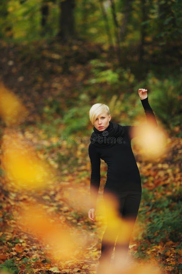 Femme dans des feuilles tombées par jets de parc d'automne photos stock