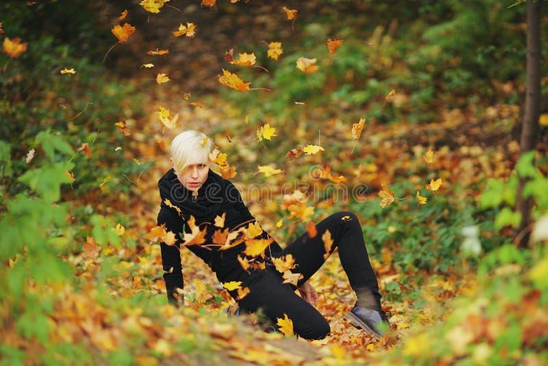 Femme dans des feuilles tombées par jets de parc d'automne image libre de droits