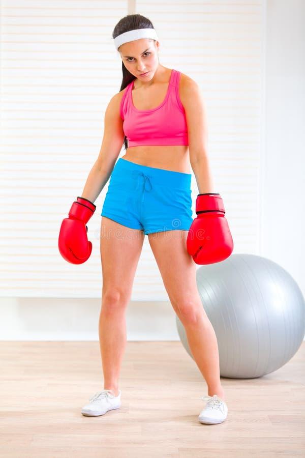 Femme dans des gants de boxe restant dans la pose fâchée images stock