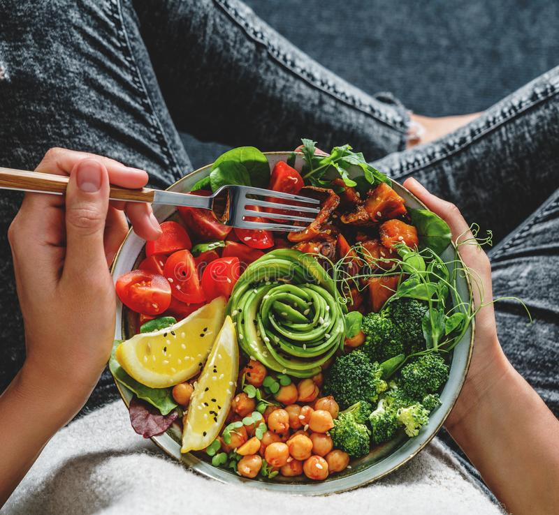 Femme dans des jeans tenant la cuvette de Bouddha avec de la salade, patates douces cuites au four, pois chiches, brocoli, verts, images stock
