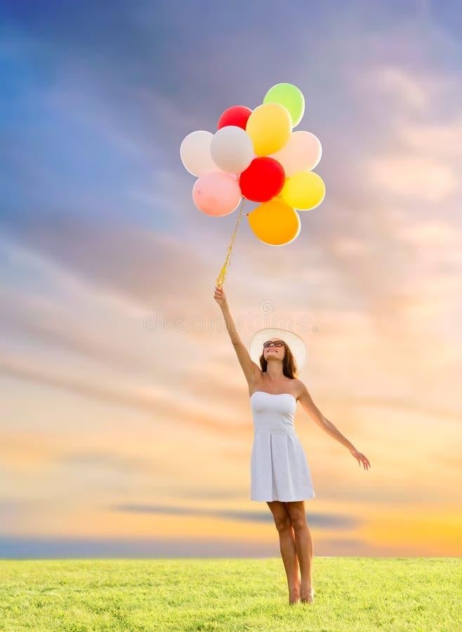 Femme dans des lunettes de soleil avec des ballons au-dessus de ciel de coucher du soleil photos stock