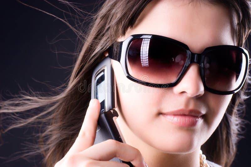 Femme dans des lunettes de soleil avec le téléphone portable images stock