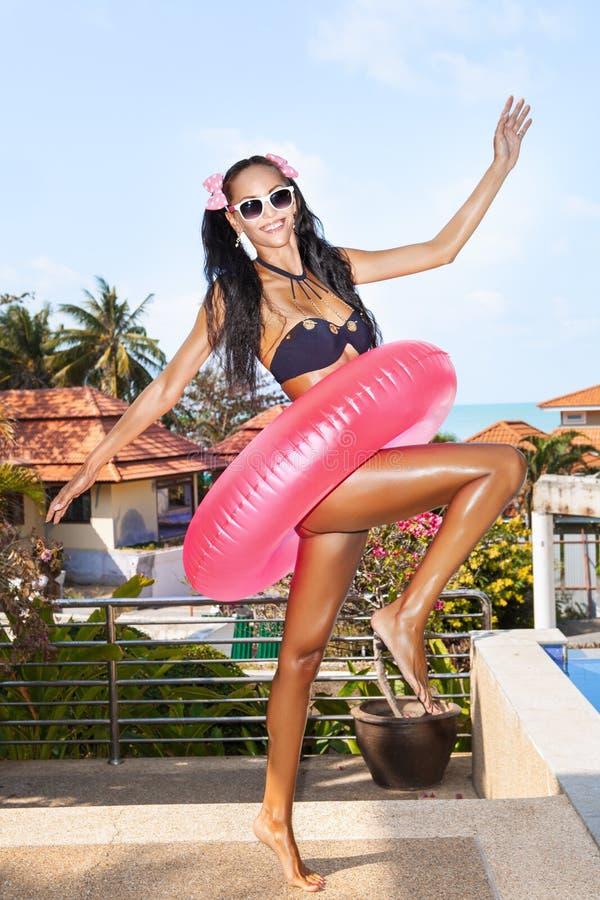 Femme dans des lunettes de soleil blanches avec la chambre à air rose photo libre de droits