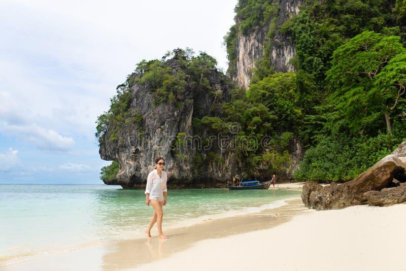 Femme dans des lunettes de soleil marchant sur la plage de mer dans des vacances d'été photo stock