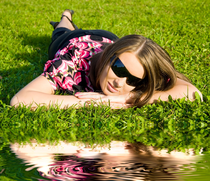 Femme dans des lunettes de soleil se reposant sur une herbe verte images libres de droits