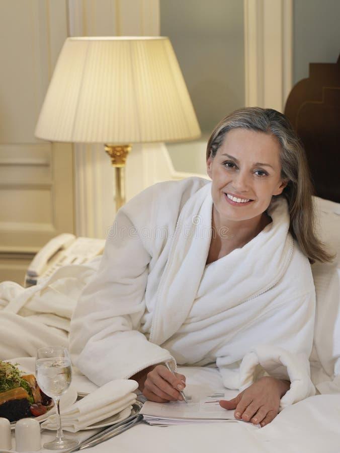 Femme dans des notes d'écriture de peignoir dans le lit images stock