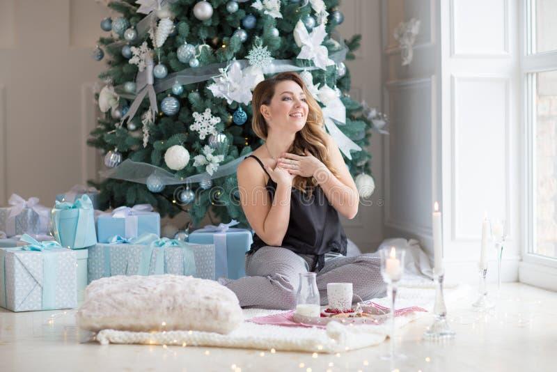Femme dans des pyjamas prenant le petit déjeuner au plancher Matin sur le ` s Ève de nouvelle année Concept de Noël photographie stock