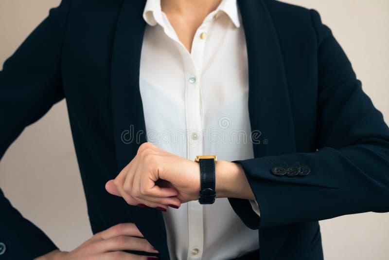 Femme dans des regards de costume sur la main de la fin d'horloge  image libre de droits