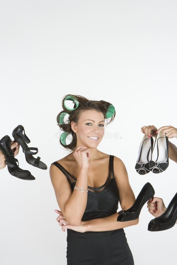 Femme dans des rouleaux avec un choix des chaussures en main photographie stock