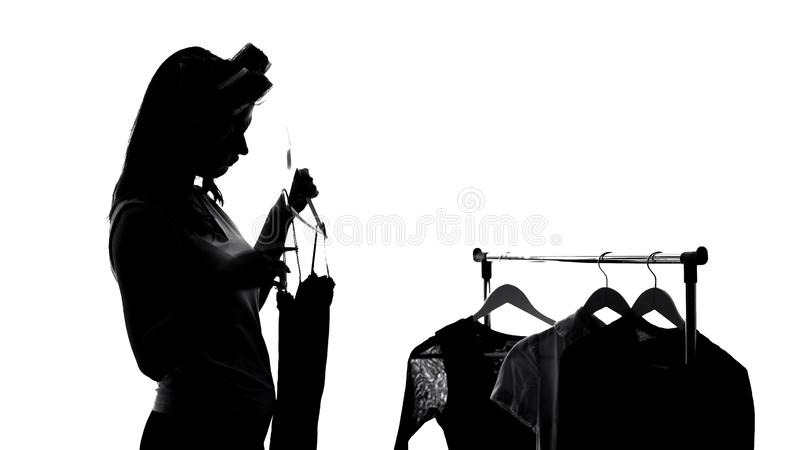 Femme dans des rouleaux de cheveux choisissant la robe, se préparant à se réunir, vêtements de mode photos libres de droits