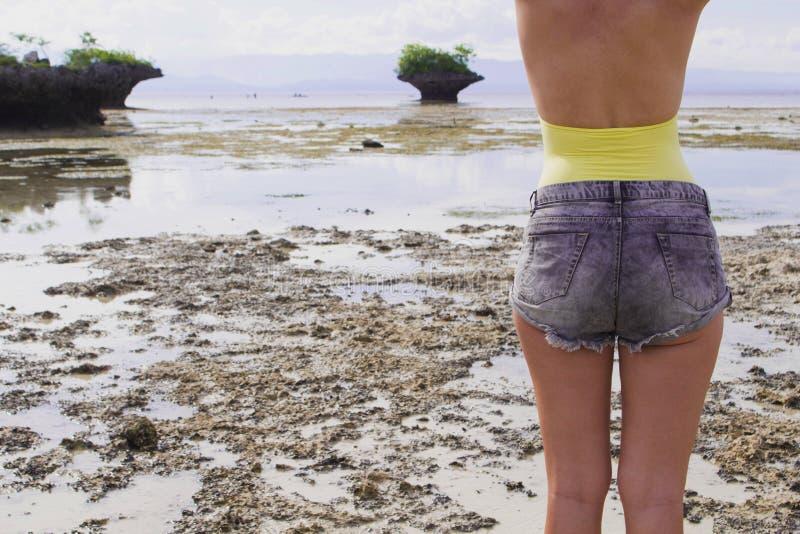 Femme dans des shorts de boho et maillot de bain sur la plage Photo modifiée la tonalité à la mode de voyage d'été image libre de droits