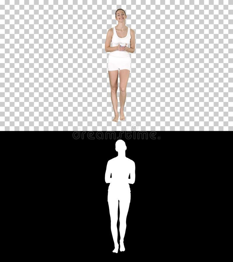 Femme dans des vêtements blancs de sport tenant une tasse de café de papier et parlant à la caméra, Alpha Channel photos stock