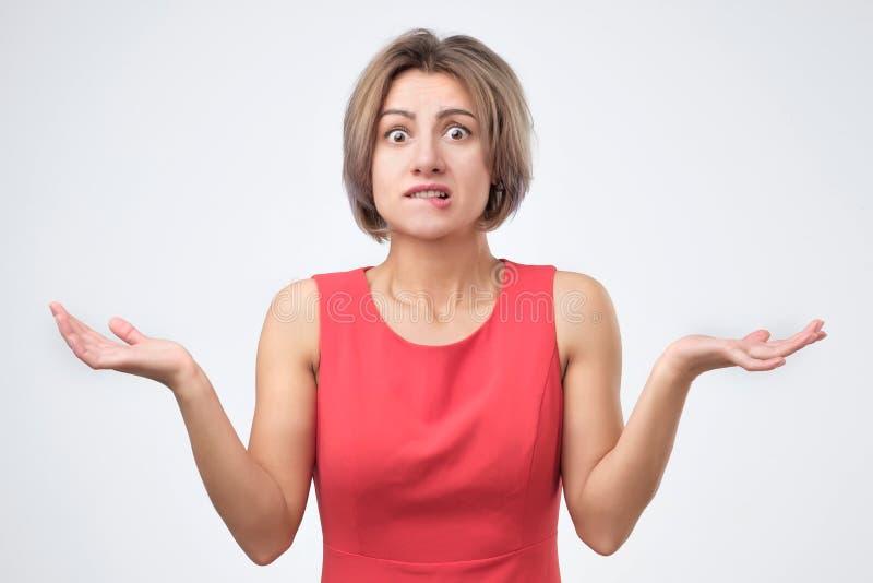 Femme dans des vêtements bleus gesticulant ses épaules, exprimant le doute, l'incertitude ou l'indifférence photos stock